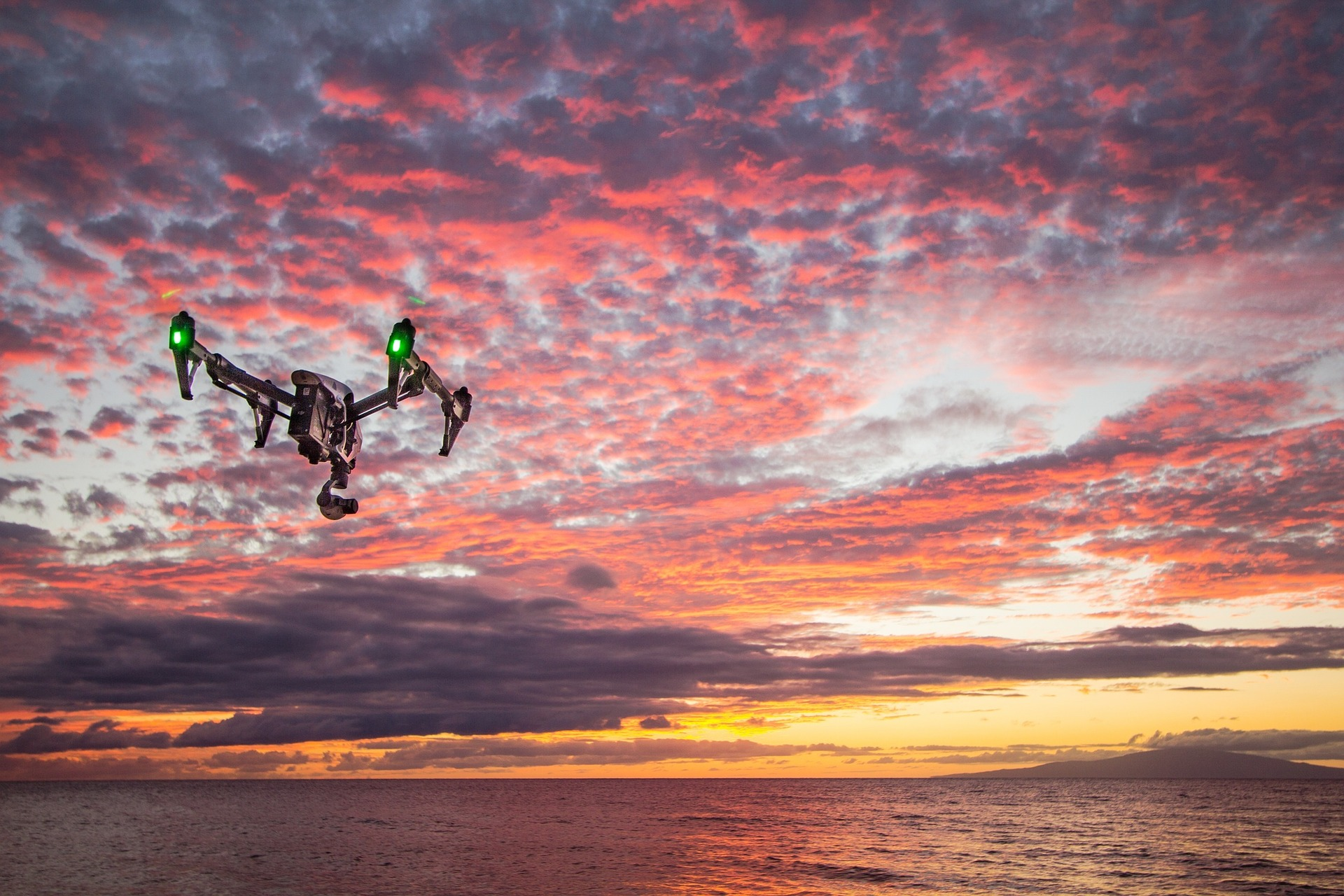 teal drone drone flying in red pink sky