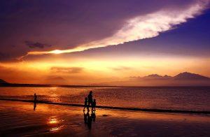 people walking on purple sunset beach