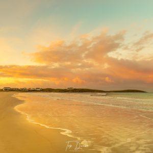 sunsetting on white shore beach